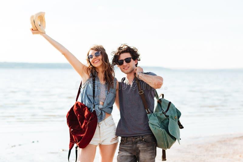 Ευτυχές νέο ζεύγος που στέκεται στην παραλία και το αγκάλιασμα στοκ φωτογραφίες