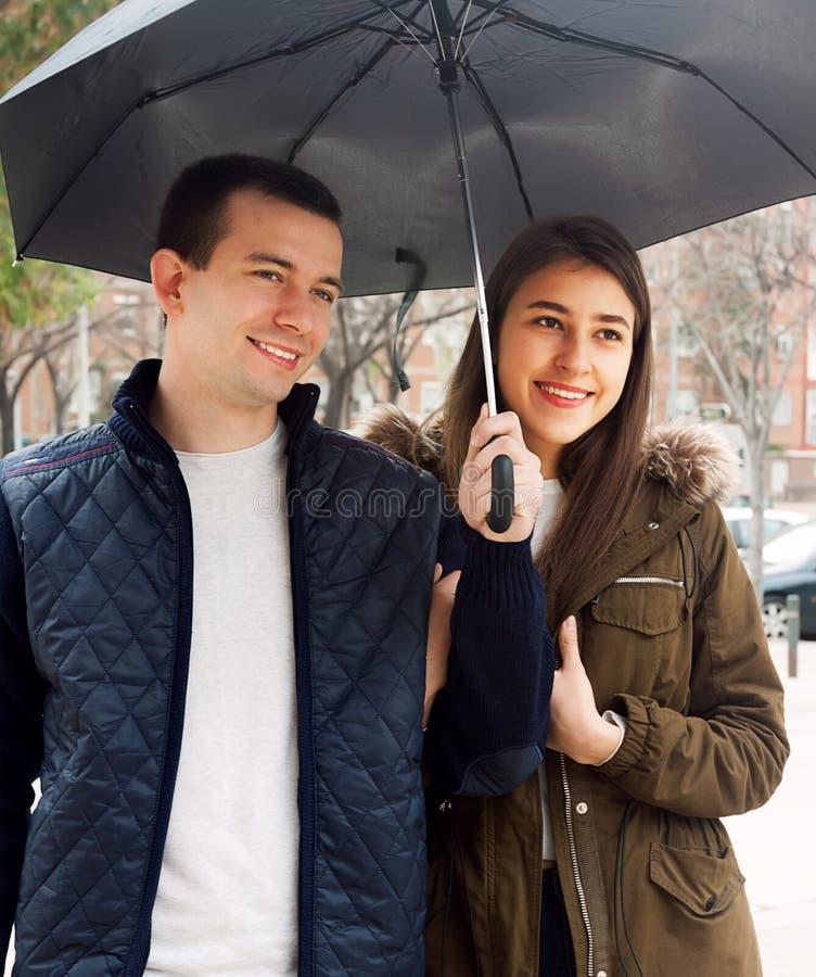 Ευτυχές νέο ζεύγος που χαμογελά κάτω από την ομπρέλα στοκ φωτογραφίες με δικαίωμα ελεύθερης χρήσης