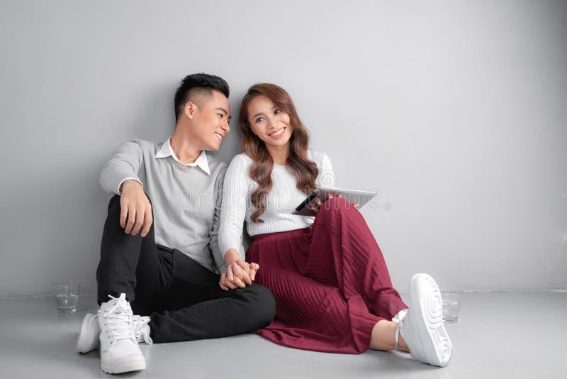 Ευτυχές νέο ζεύγος που χρησιμοποιεί τη συνεδρίαση ταμπλετών στο πάτωμα στο σπίτι στο γκρίζο υπόβαθρο στοκ φωτογραφία με δικαίωμα ελεύθερης χρήσης