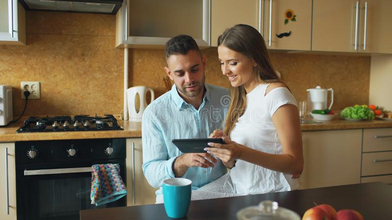 Ευτυχές νέο ζεύγος που χρησιμοποιεί τον ψηφιακό υπολογιστή ταμπλετών ενώ καθμένος στην κουζίνα και έχοντας το πρόγευμα το πρωί στοκ εικόνες