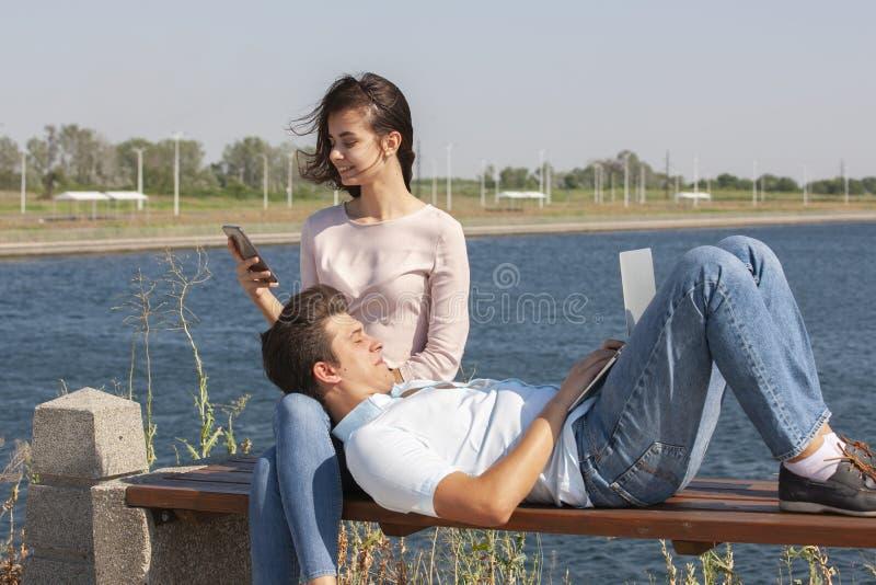 Ευτυχές νέο ζεύγος που χρησιμοποιεί το lap-top καθμένος μαζί στο πάρκο στοκ φωτογραφία