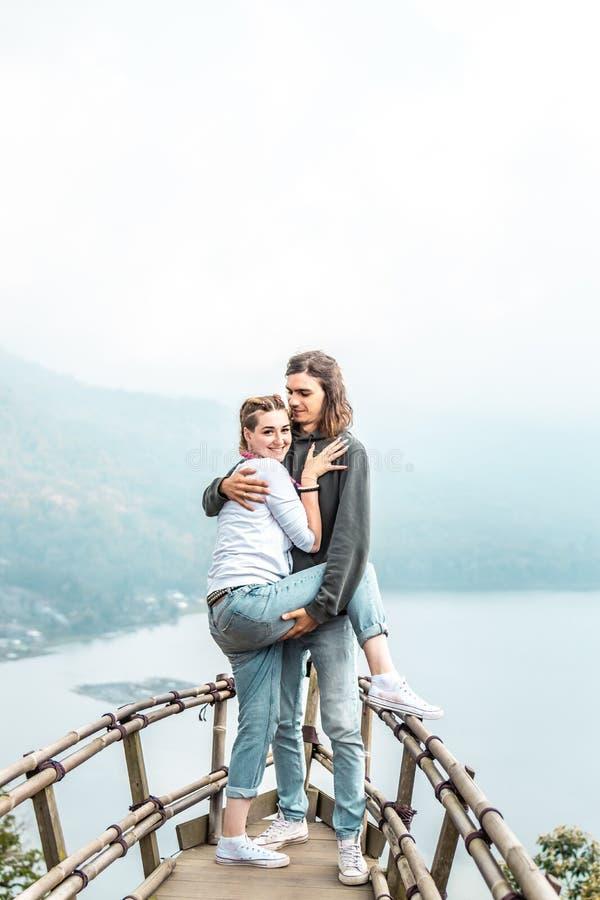 Ευτυχές νέο ζεύγος των τουριστών στην ξύλινη γέφυρα με το τροπικό υπόβαθρο Λίμνη Νησί του Μπαλί στοκ φωτογραφία