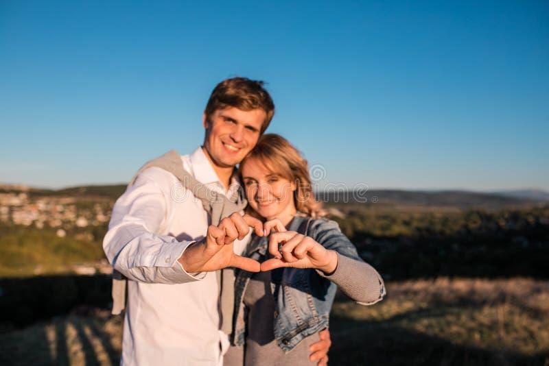 Ευτυχές νέο ζεύγος ` s που κατασκευάζει την καρδιά των δάχτυλων στοκ εικόνα