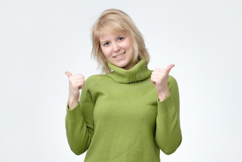 Ευτυχές νέο καυκάσιο θηλυκό που φορά το πράσινο πουλόβερ που αποτελεί τον αντίχειρα να υπογράψει και που χαμογελά χαρωπά στοκ εικόνες