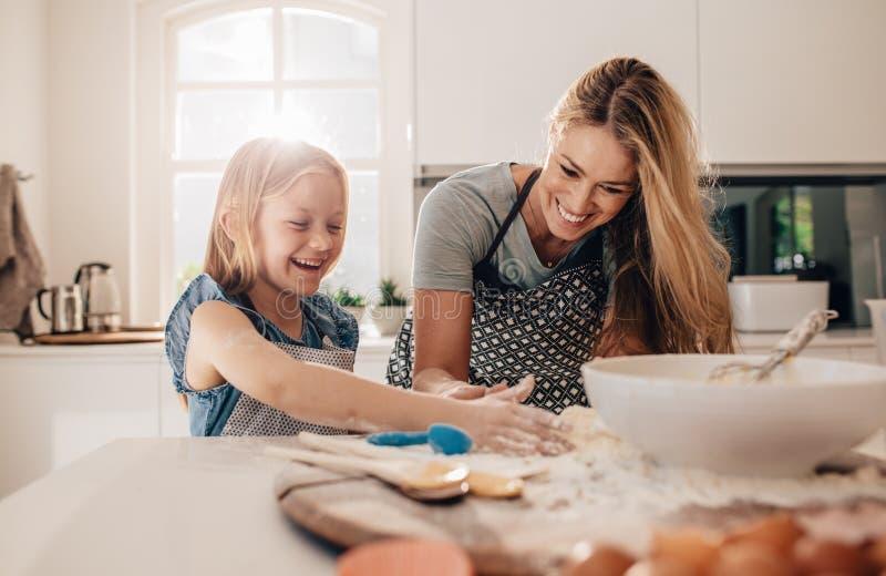 Ευτυχές νέο κορίτσι με τη μητέρα της που κατασκευάζει τη ζύμη στοκ εικόνες με δικαίωμα ελεύθερης χρήσης