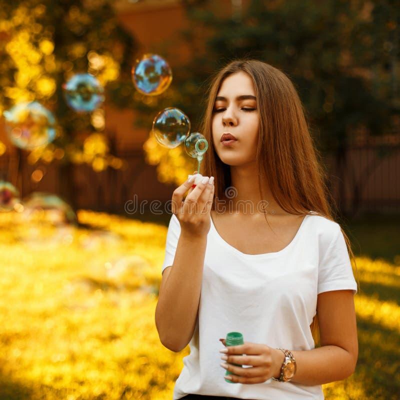 Ευτυχές νέο κορίτσι με τις φυσαλίδες σαπουνιών στις θερινές διακοπές στο ηλιοβασίλεμα στοκ εικόνες με δικαίωμα ελεύθερης χρήσης