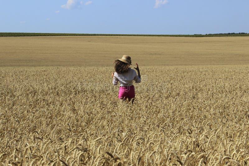 Ευτυχές νέο κορίτσι που περπατά σε ένα λιβάδι σίτου στοκ φωτογραφίες