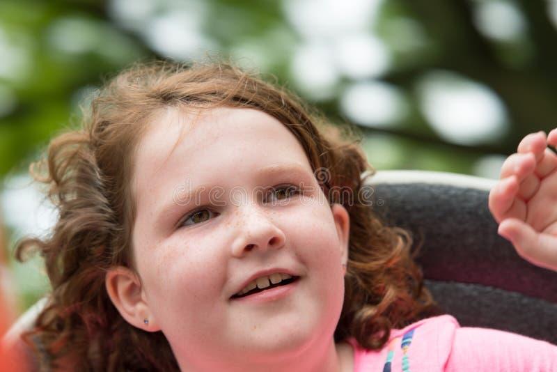 Ευτυχές νέο κορίτσι στο γύρο διασκέδασης με την τρίχα που φυσά στον αέρα στοκ εικόνες