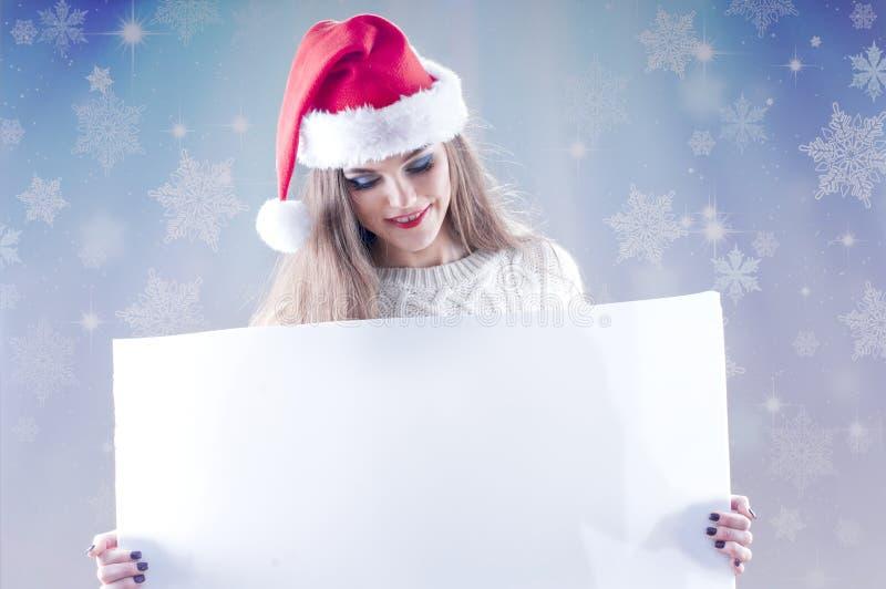 Ευτυχές νέο κορίτσι Χριστουγέννων που κρατά ένα κενό σημάδι εγγράφου στοκ εικόνες