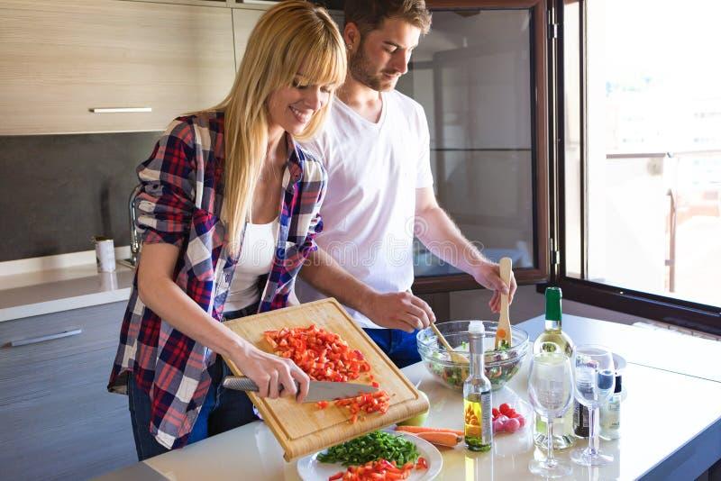 Ευτυχές νέο μαγείρεμα ζευγών μαζί στην κουζίνα στο σπίτι στοκ εικόνες με δικαίωμα ελεύθερης χρήσης