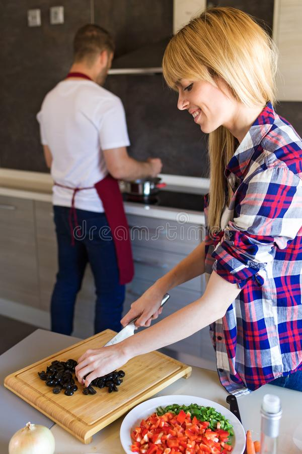 Ευτυχές νέο μαγείρεμα ζευγών μαζί στην κουζίνα στο σπίτι στοκ εικόνα