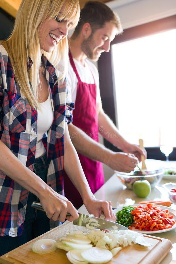 Ευτυχές νέο μαγείρεμα ζευγών μαζί στην κουζίνα στο σπίτι στοκ εικόνα με δικαίωμα ελεύθερης χρήσης