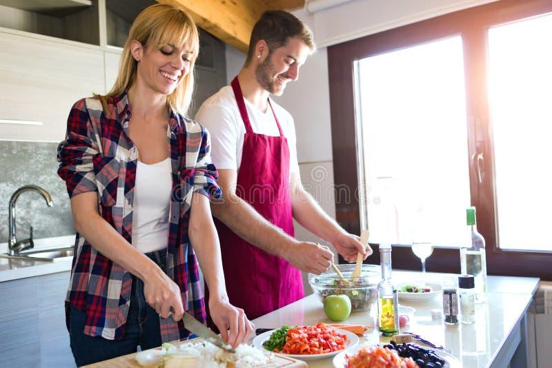 Ευτυχές νέο μαγείρεμα ζευγών μαζί στην κουζίνα στο σπίτι στοκ φωτογραφίες με δικαίωμα ελεύθερης χρήσης