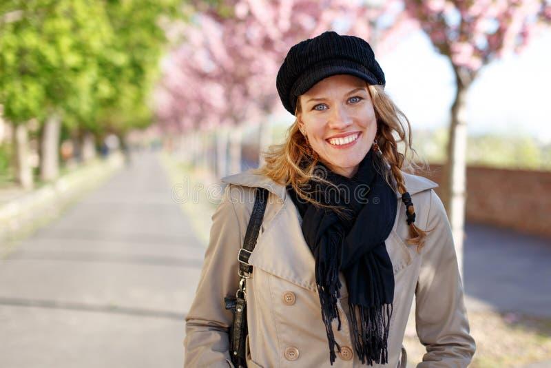 Ευτυχές νέο οδοντωτό χαμόγελο γυναικών στο πρώιμο ελατήριο στοκ εικόνα