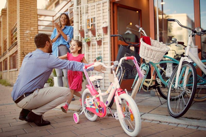Ευτυχές νέο ποδήλατο κορών χαμόγελου αγορών πατέρων στο κατάστημα στοκ φωτογραφία