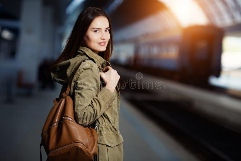 Ευτυχές νέο τραίνο γυναικών waitng στην πλατφόρμα σιδηροδρομικών σταθμών Ταξίδι γυναικών με το τραίνο στοκ εικόνα με δικαίωμα ελεύθερης χρήσης