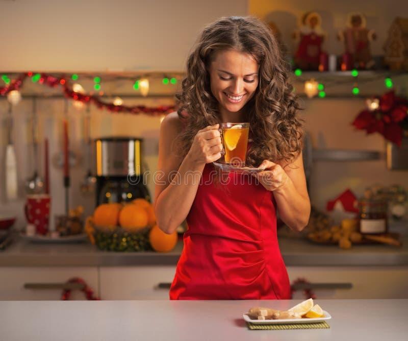 Ευτυχές νέο τσάι πιπεροριζών κατανάλωσης γυναικών στην κουζίνα στοκ εικόνα
