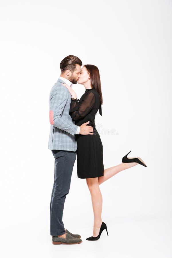 Ευτυχές νέο φίλημα ζευγών αγάπης που απομονώνεται πέρα από το άσπρο υπόβαθρο στοκ εικόνα