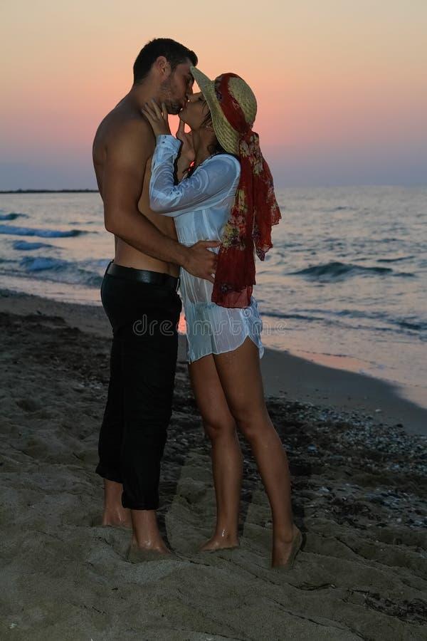 Ευτυχές νέο φίλημα ζευγών στην παραλία στο σούρουπο στοκ φωτογραφία με δικαίωμα ελεύθερης χρήσης