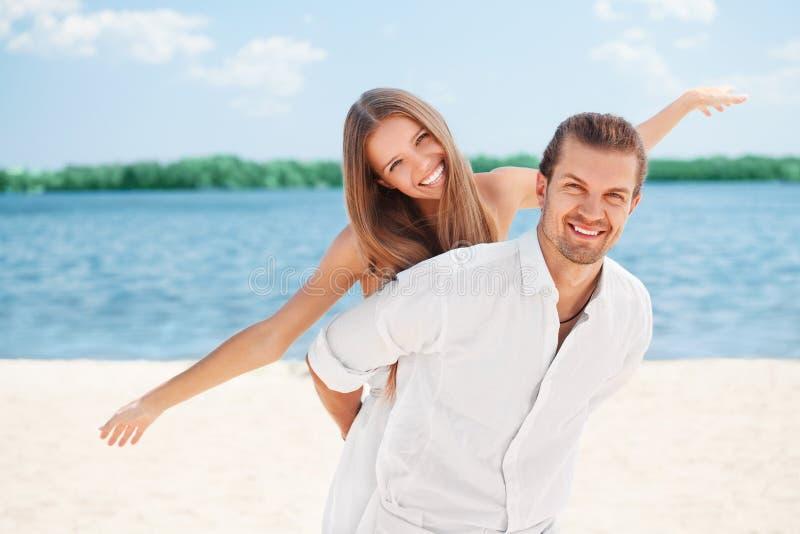 Ευτυχές νέο χαρούμενο ζεύγος που έχει piggybacking διασκέδασης παραλιών που γελά μαζί κατά τη διάρκεια των διακοπών καλοκαιρινών  στοκ εικόνα