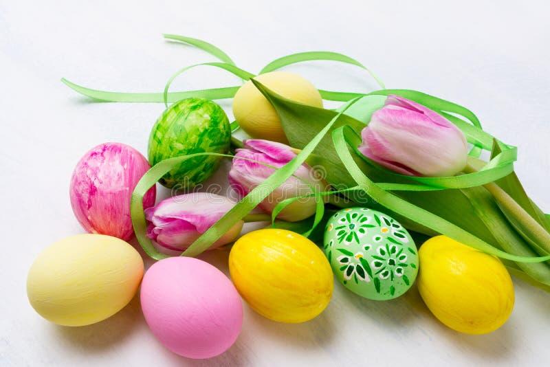 Ευτυχές ντεκόρ Πάσχας με τα πράσινες, κίτρινες, ρόδινες αυγά και τις τουλίπες στοκ φωτογραφία