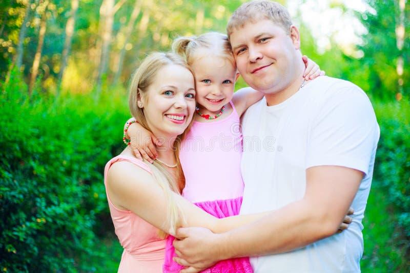 Ευτυχές ξανθό νέο οικογενειακό υπαίθριο αγκάλιασμα στοκ φωτογραφίες με δικαίωμα ελεύθερης χρήσης