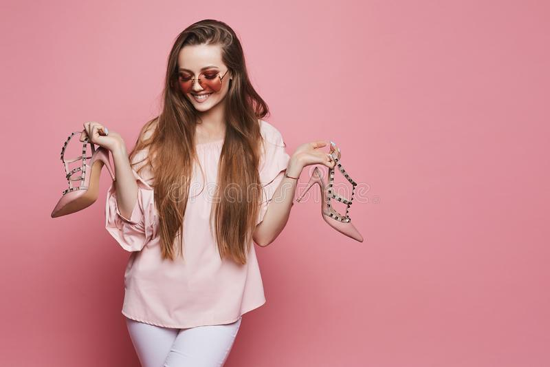 Ευτυχές ξανθό πρότυπο κορίτσι με ένα λαμπρό χαμόγελο στην μπεζ μπλούζα και στα μοντέρνα ρόδινα γυαλιά ηλίου που κρατούν τα μοντέρ στοκ φωτογραφίες