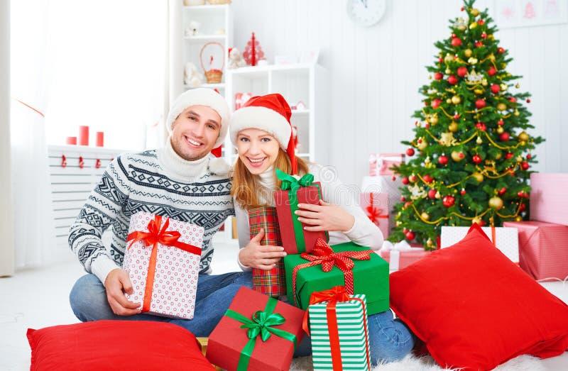 Ευτυχές οικογενειακό ζεύγος με ένα δώρο στα Χριστούγεννα στο σπίτι στοκ εικόνα με δικαίωμα ελεύθερης χρήσης