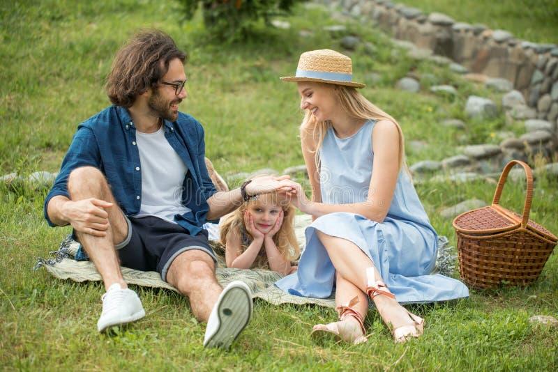 Ευτυχές οικογενειακό υπαίθρια με τη χαριτωμένη κόρη τους, μπλε ενδύματα, γυναίκα στο καπέλο στοκ φωτογραφίες με δικαίωμα ελεύθερης χρήσης