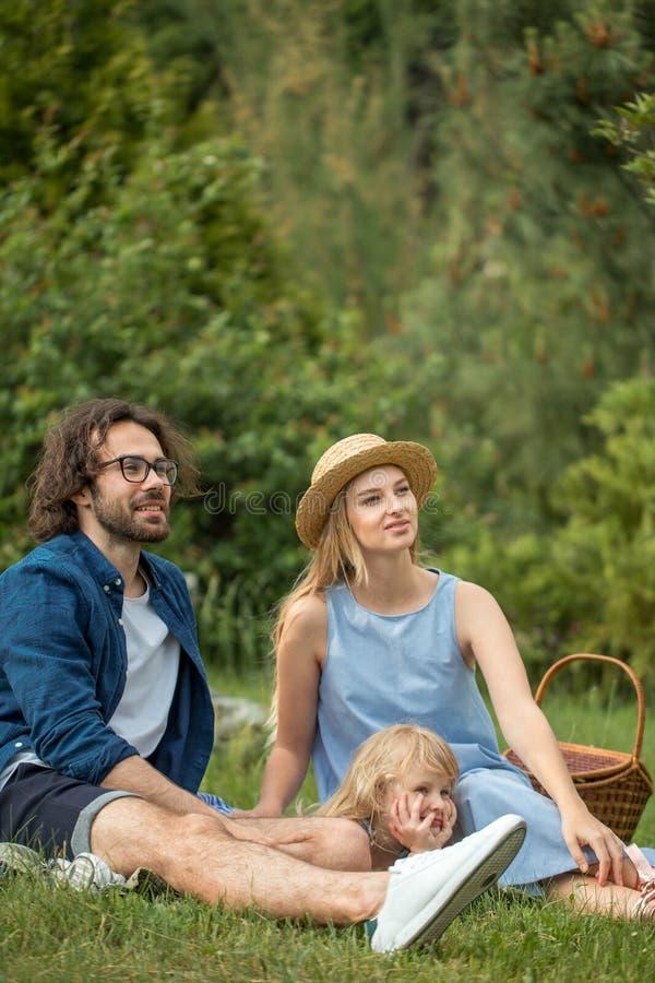 Ευτυχές οικογενειακό υπαίθρια με τη χαριτωμένη κόρη τους, μπλε ενδύματα, γυναίκα στο καπέλο στοκ φωτογραφία με δικαίωμα ελεύθερης χρήσης