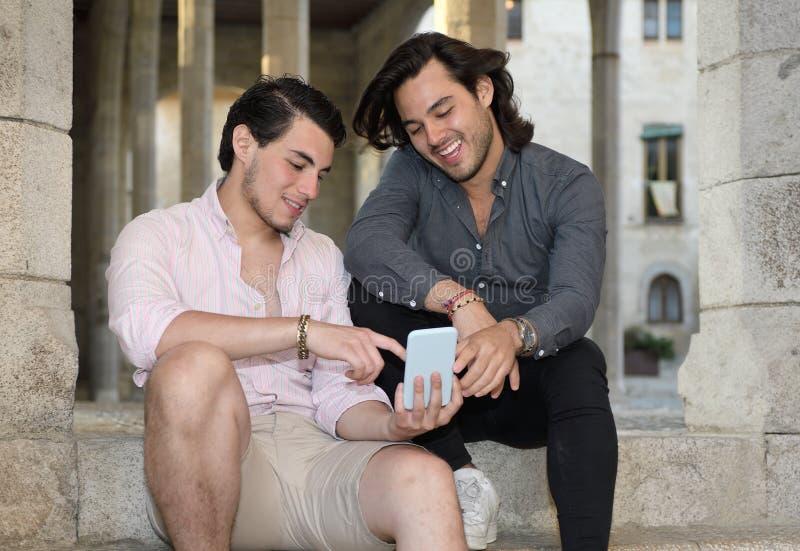 Ευτυχές ομοφυλοφιλικό ζεύγος με το κινητό τηλέφωνό τους στοκ φωτογραφία
