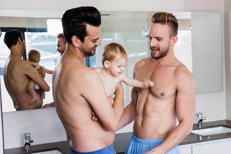 Ευτυχές ομοφυλοφιλικό ζεύγος που κρατά το παιδί τους στοκ φωτογραφία