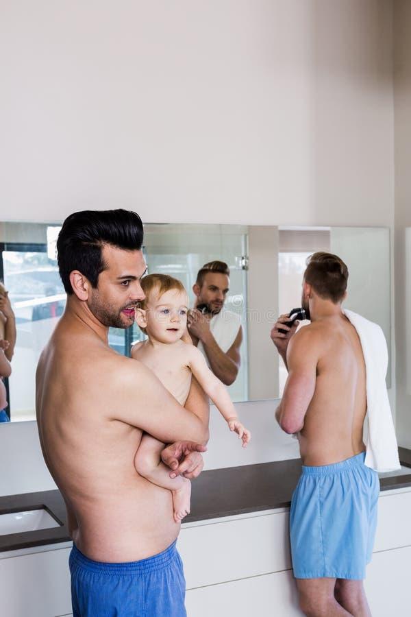 Ευτυχές ομοφυλοφιλικό ζεύγος που ξυρίζει και που κρατά το παιδί τους στοκ φωτογραφία με δικαίωμα ελεύθερης χρήσης