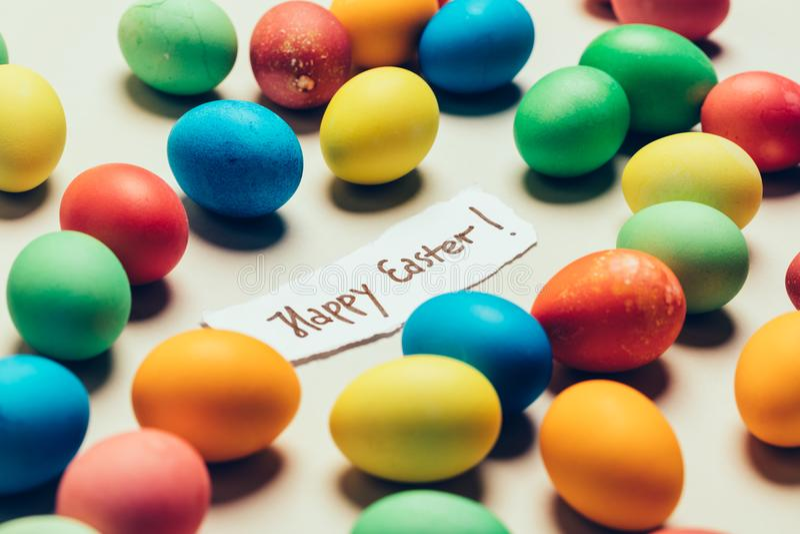 ` Ευτυχές Πάσχας γράψιμο ` και δέσμη των ζωηρόχρωμων βαμμένων αυγών στοκ φωτογραφία