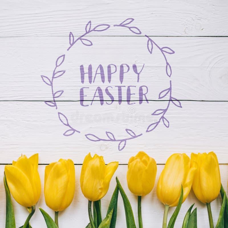 Ευτυχές Πάσχας κείμενο καλλιγραφίας χεριών γράφοντας Κίτρινη δέσμη τουλιπών στο άσπρο ξύλινο αγροτικό επιτραπέζιο υπόβαθρο σιταπο στοκ εικόνες