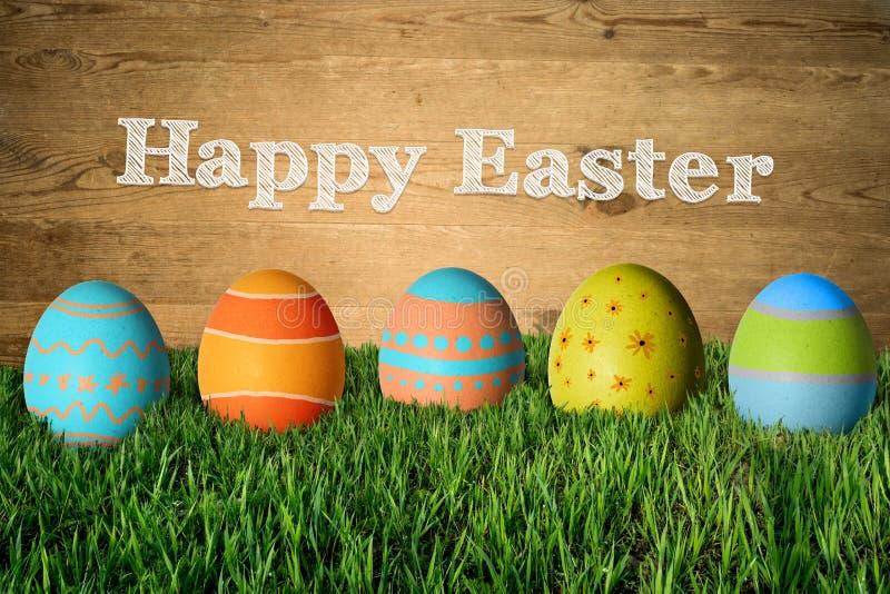 Ευτυχές Πάσχα και χρωματισμένα ζωηρόχρωμα αυγά στη χλόη στοκ εικόνες με δικαίωμα ελεύθερης χρήσης