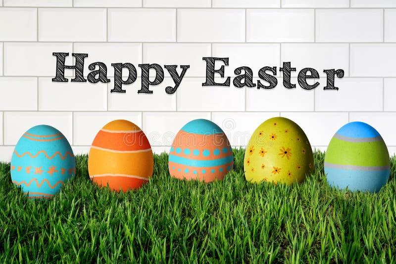 Ευτυχές Πάσχα και χρωματισμένα ζωηρόχρωμα αυγά στη χλόη στοκ εικόνες