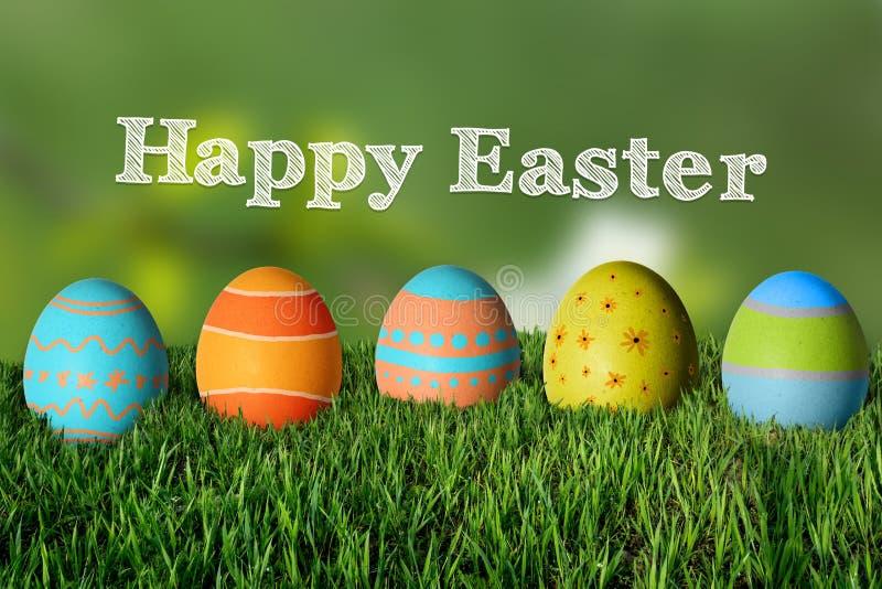 Ευτυχές Πάσχα και χρωματισμένα ζωηρόχρωμα αυγά στη χλόη στοκ φωτογραφίες