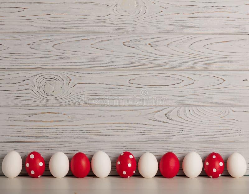 Ευτυχές Πάσχα! Χρωματισμένα αυγά Πάσχας - κόκκινο, λευκό και κόκκινο με τα άσπρα σημεία Πόλκα σε ένα γκρίζο ξύλινο υπόβαθρο στοκ φωτογραφία με δικαίωμα ελεύθερης χρήσης