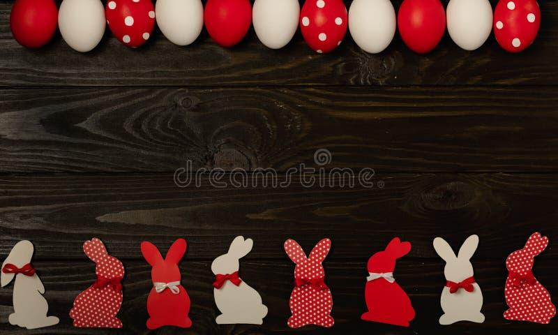 Ευτυχές Πάσχα! Χρωματισμένες αυγά Πάσχας και διακόσμηση Πάσχας - λαγουδάκια Πάσχας με τις κορδέλλες - κόκκινο, λευκό και κόκκινο  στοκ εικόνες