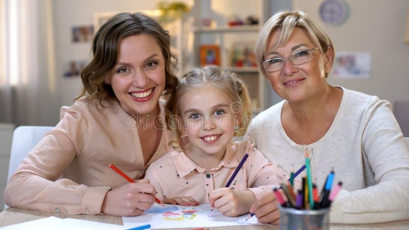 Ευτυχές παιδί με τα μολύβια σχεδίων μητέρων και γιαγιάδων που χαμογελά στη κάμερα, οικογένεια στοκ εικόνες
