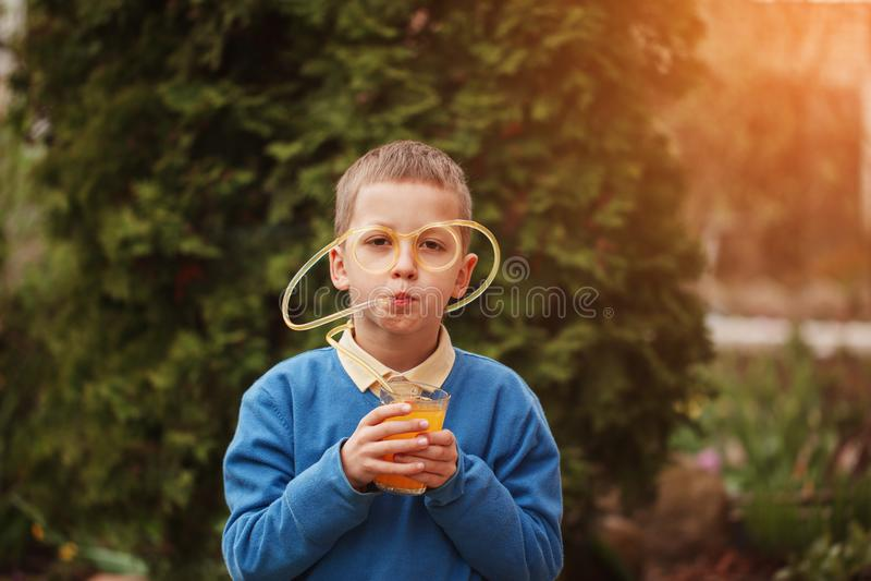 Ευτυχές παιδί πορτρέτου που πίνει το χυμό από πορτοκάλι στη θερινή ημέρα στοκ εικόνα