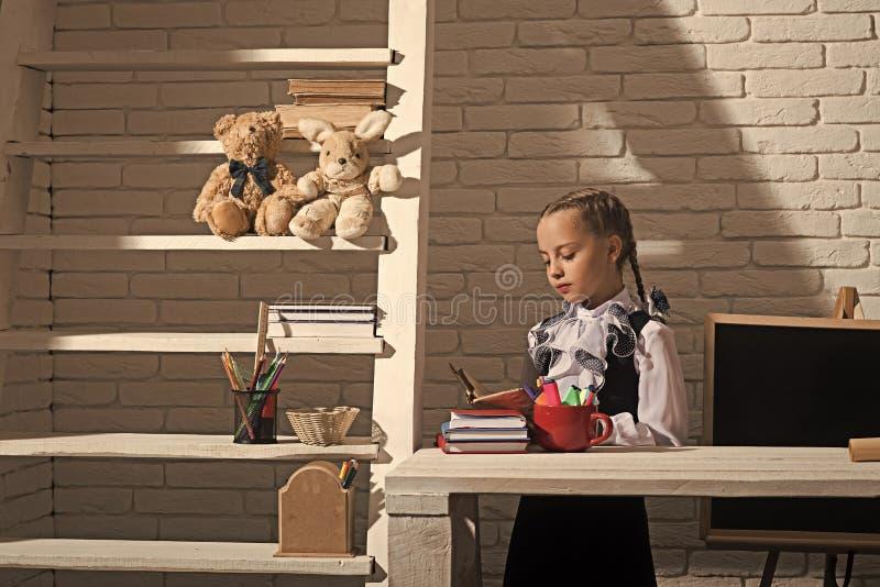 Ευτυχές παιδί που έχει τη διασκέδαση Η μαθήτρια με το συγκεντρωμένο πρόσωπο κρατά το ανοικτό βιβλίο στοκ φωτογραφίες