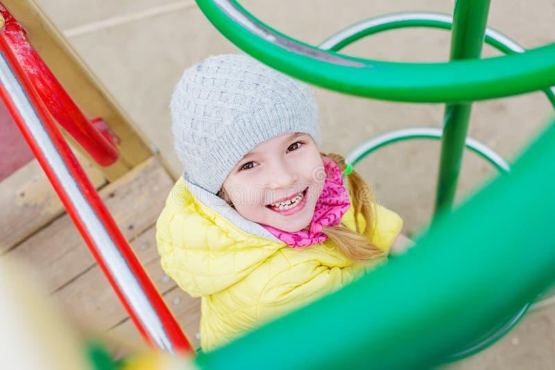 Ευτυχές παιδί που έχει τη διασκέδαση στην παιδική χαρά στοκ εικόνες