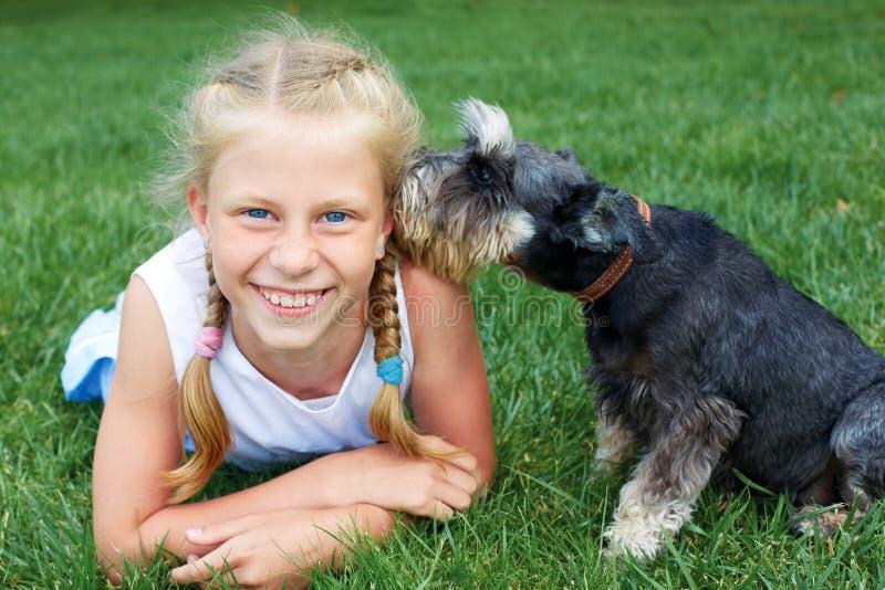 Ευτυχές παιδί που βρίσκεται στη χλόη με το σκυλί της στο πάρκο Το SEC στοκ εικόνες
