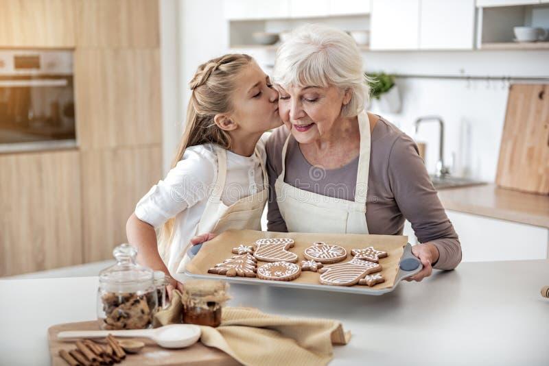 Ευτυχές παιδί που ευχαριστεί το grandma για τη γλυκιά ζύμη στοκ φωτογραφία
