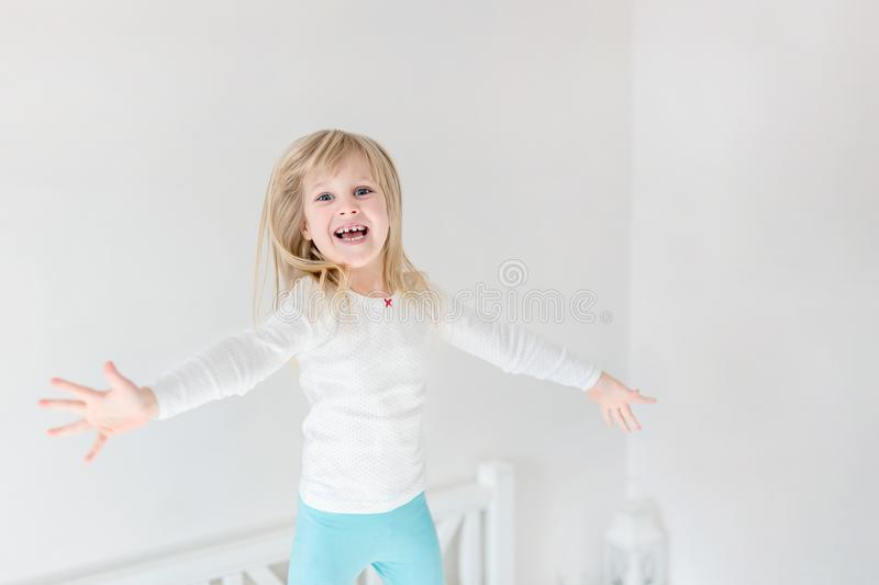 Ευτυχές παιδί που πηδά πέρα από το κρεβάτι Χαριτωμένος λίγο ξανθό κορίτσι που έχει τη διασκέδαση στο εσωτερικό Ευτυχής και απρόσε στοκ φωτογραφία με δικαίωμα ελεύθερης χρήσης