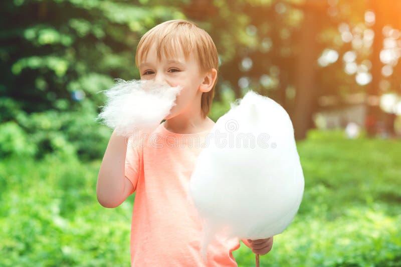 Ευτυχές παιδί που τρώει την καραμέλα βαμβακιού Χαριτωμένο μικρό παιδί υπαίθρια E στοκ εικόνες με δικαίωμα ελεύθερης χρήσης