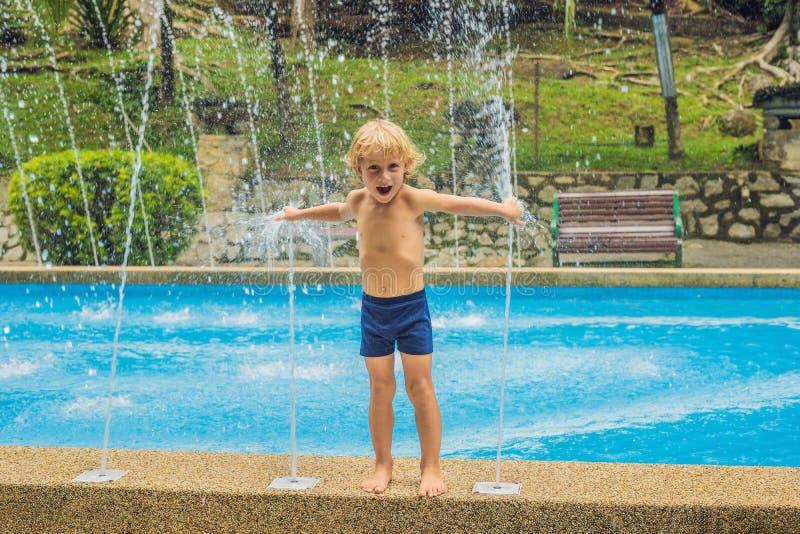 Ευτυχές παιχνίδι αγοριών με την πηγή νερού στη λίμνη στοκ εικόνες με δικαίωμα ελεύθερης χρήσης