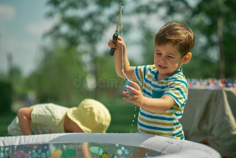 Ευτυχές παιχνίδι αγοριών μικρών παιδιών στην αλιεία καυτή θερινή ημέρα παιδιά που παίζουν έξω στοκ εικόνες με δικαίωμα ελεύθερης χρήσης